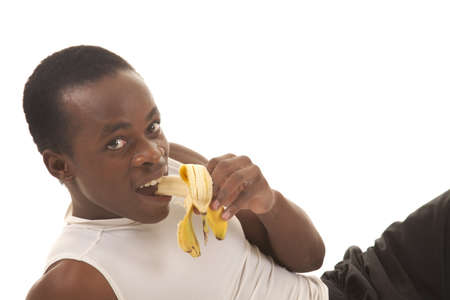 banana: A man after a workout taking a bite out of a banana