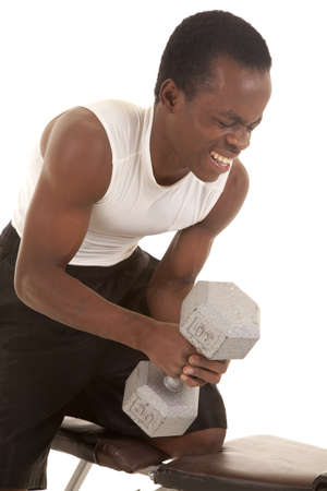 heavy weight: A man trying to lift a heavy weight with a painful expression on his face.