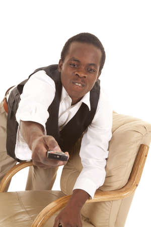 A man leaning over a chair with a remote trying to get it to change a channel photo