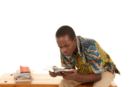 A man sitting on a bench with a stack of books looking at a book with a confused expression on his face. photo