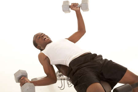 A man laying on a workout bench holding too much weight almost to fall off the bench. photo