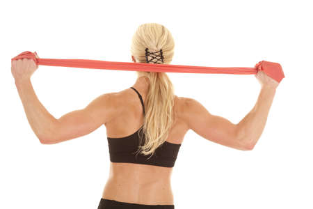 A woman stretching her shoulders with a red band. photo