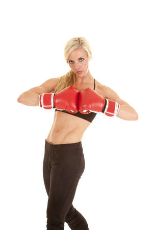 A woman standing with her boxing gloves together with a serious expression on her face.