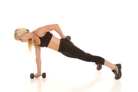A woman doing  a one arm push up with her weights. photo