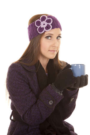 a woman holding on to her cup while wearing her winter coat and hat. Stock Photo - 16242793