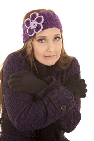 A woman in her winter clothes shivering because she is cold.