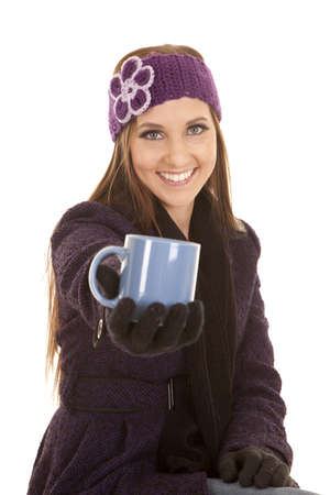 a woman smiling in her winter clothes holding out her cup. Stock Photo - 16242803