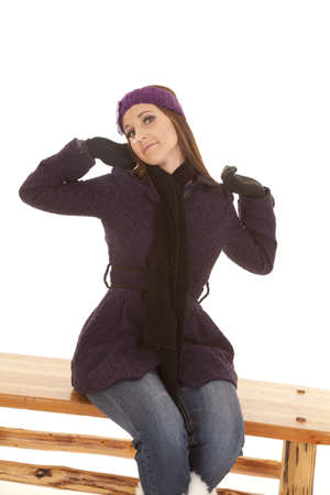 a woman sitting on a bench stretching while wearing her winter coat. Stock Photo - 16242804