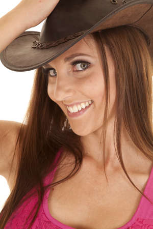 A close up of a woman with a big smile on her lips with her pink tank and cowgirl hat. photo