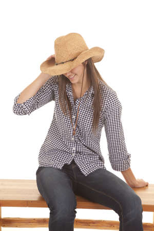 A woman looking down and holding onto her hat with a smile on her lips photo