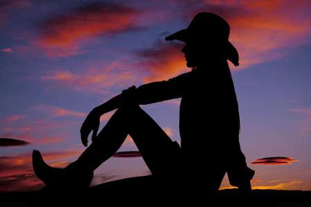 wild hair: Una cowgirl bella donna seduta e guardando il terreno con un bellissimo tramonto.