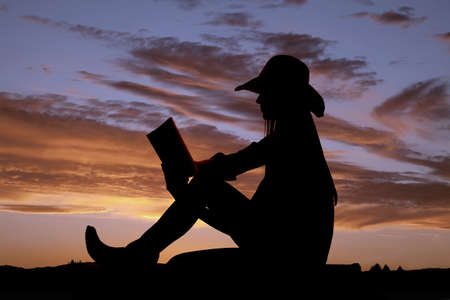 A cowgirl sitting and reading her book out in nature. Standard-Bild