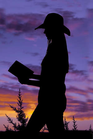 A woman walking and reading with a beautiful sunset in the background. photo
