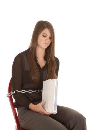 A woman with a frustrated expression on her face being chained to either to a job or school. photo