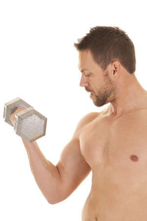 A man working out  with out a shirt on and with a weight looking down at his arm. photo