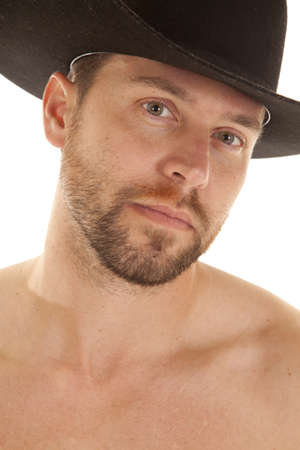 A close up of a cowboys face with his black hat on and no shirt on. photo