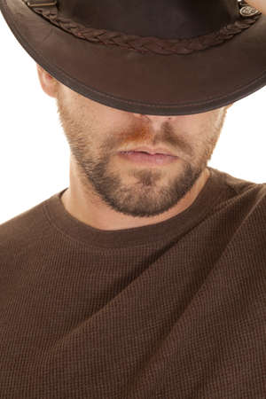 A close up of a man in his brown shirt and cowboy hat with a serious expression on his face photo