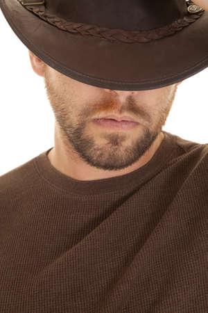 muscle shirt: Un primer plano de un hombre en camisa marr�n y un sombrero de vaquero con una expresi�n seria en su cara Foto de archivo