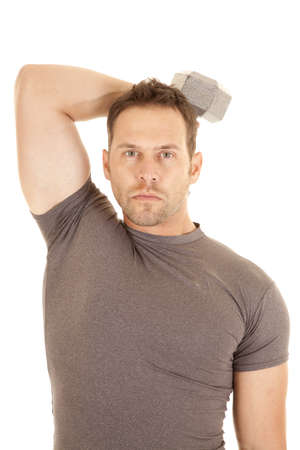 A man working out his triceps with a weight and a serious expression. photo