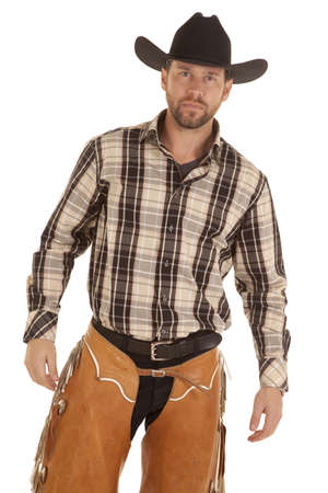 A cowboy in his western chaps and plaid shirt with his black hat on his head looking serious.