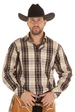 A cowboy with a serious expression holding onto his belt