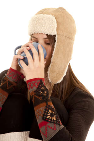 A woman drinking something from a mug in her warm clothing. photo
