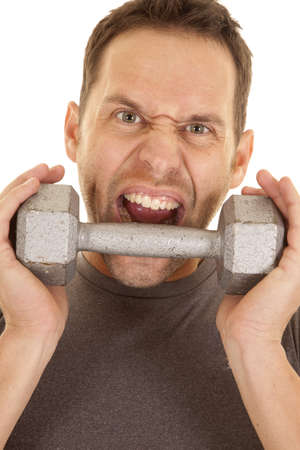 a close up of a mans face with a crazy expression on his face getting ready to bite a weight. photo