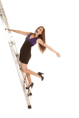 a woman trying to climb the ladder to success and feeling like she is going to fall. Stok Fotoğraf