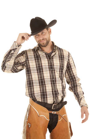 A cowboy holding on to the brim of his hat with a smile on his face.