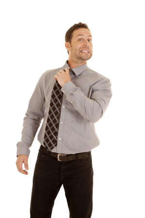 loosen: A business man with a funny expression on his face holding on to his tie loosing the tie. Stock Photo