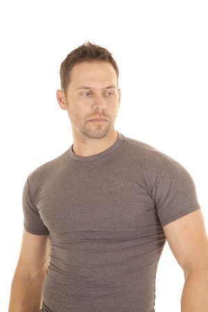 A man in his gray tight fitted shirt with a serious expression on his face. photo