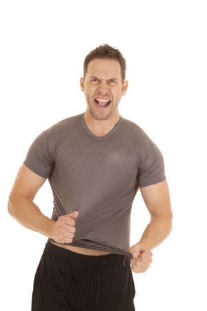athletic wear: A man trying to rip off his tight fitting shirt.
