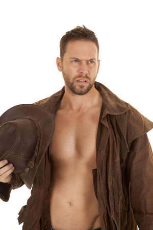 A cowboy with his shirt off and his duster on holding on to his hat looking away. photo