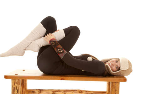 A woman laying on her bench in her warm long johns, long socks and a warm hat. Stock Photo - 18187168