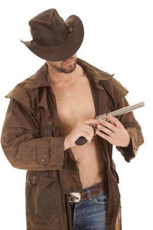 sexy cowboy: A man in his western duster holding on to his weapon. Stock Photo