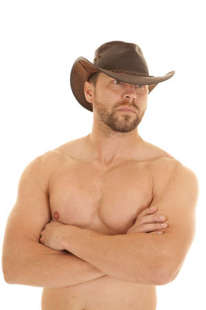 A cowboy with his arms folded across his chest with a serious expression on his face. photo
