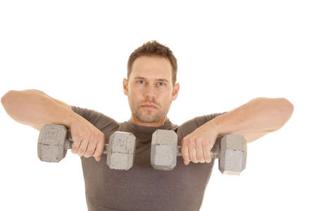 A man lifting weights working out his shoulders with a serious expression on his face. photo