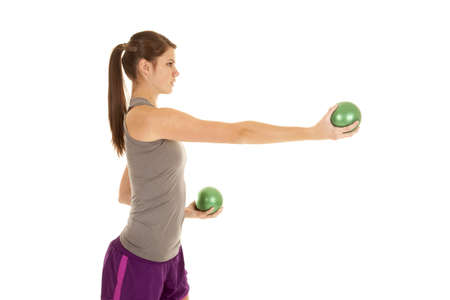 weighted: A woman working out by using her green weighted balls.