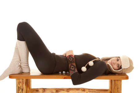 A woman laying on her bench in her warm long johns, long socks and a warm hat.