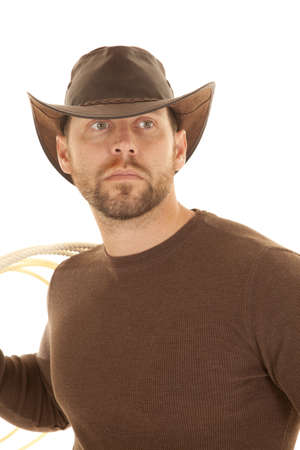 A cowboy in his brown shirt and hat holding on to a rope. photo