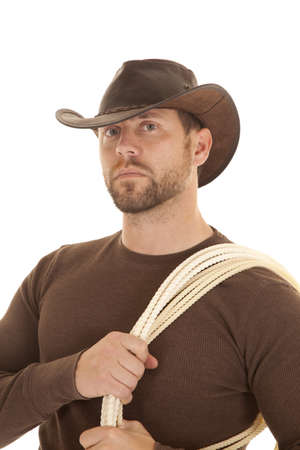 A cowboy in his brown shrit and hat with a rope on his shoulder. photo
