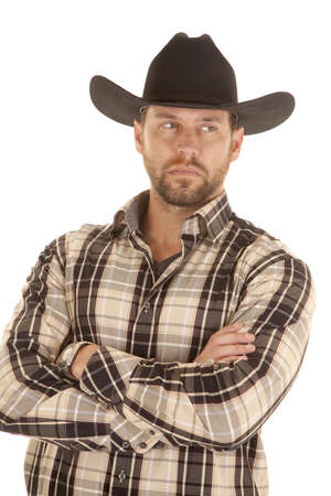 rugged man: A man in his plaid shirt and black western hat with a serious expression on his face.