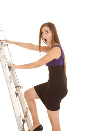 A woman with a shocked expression on her face climbing the ladder to success either in school or work. photo