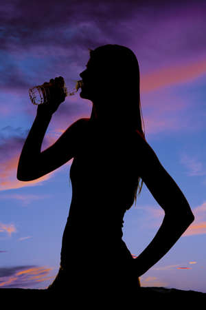 A silhouette of a woman getting a drink from a water bottle. photo