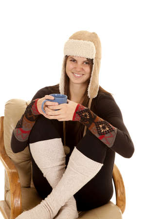 A woman sitting in her chair in her warm clothes and hat holding on to a mug with a warm drink. photo