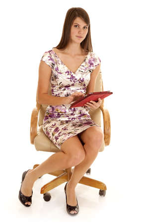 A woman sitting in her chair working on her tablet. photo