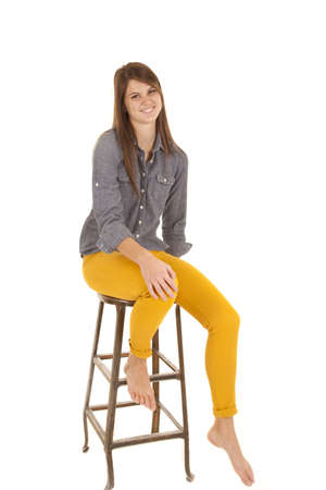 A woman sitting on her stool in her yellow pants ad gray top with a smile on her face. photo