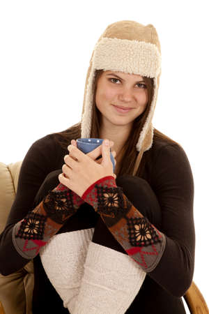long johns: A woman curled up and warm holding on to her mug with a smile on her face.