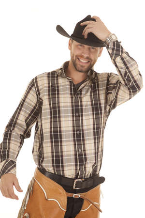 a cowboy in his western gear with a smile on his face holding on to his hat.