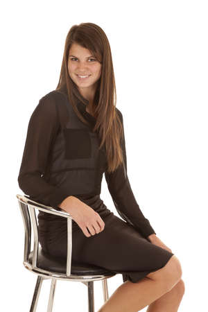 stool: a woman sitting in her stool with a smile on her face in her black power dress.